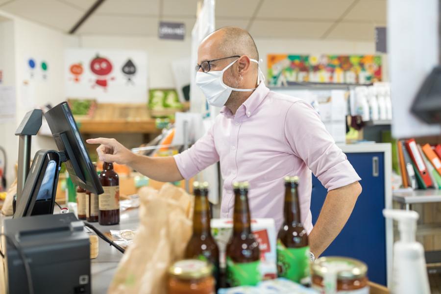 Breizhicoop - coopérat.rice.eur.s au travail : le passage en caisse des produits par un coopérateur bénévole